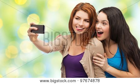 technology, friendship and people concept - two smiling teenage girls or young women taking selfie with smartphone over green lights background