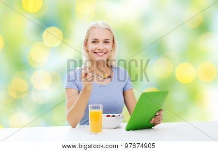 healthy eating, dieting and people concept - smiling young woman with tablet pc computer eating breakfast over summer green holidays lights background
