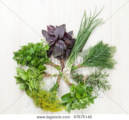 Fresh garden herbs on wooden table. Top view