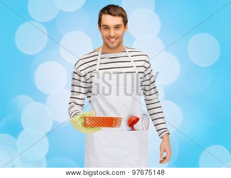 people, cooking, culinary and food concept - happy man or cook in apron with baking and kitchenware over blue lights background