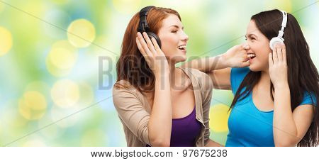 music and technology concept - two laughing teenage girls or young women with headphones listening to music over green lights background