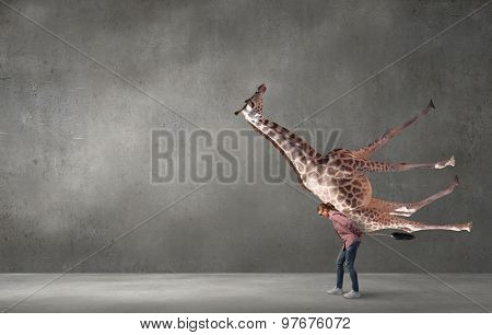 Funny young girl holding giraffe animal in hands