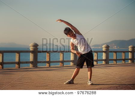 Vietnamese Boy Does Bending Aside On Embankment At Dawn