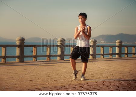 Vietnamese Boy Bends Downward On Embankment At Dawn