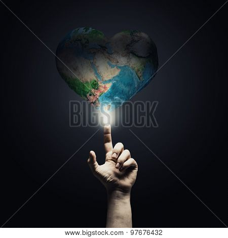 Human hand pointing with finger on Earth planet. Elements of this image are furnished by NASA
