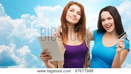 online shopping, e-money, commerce, people and technology concept - two smiling teenage girls or young women with tablet pc computer and credit card over blue sky with clouds background