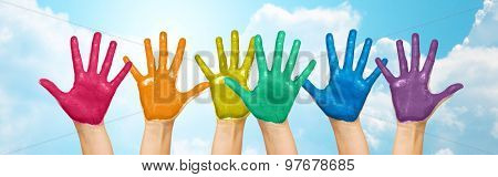 people, gay pride, creativity and art concept - palms of human hands painted in rainbow colors over blue sky and clouds background