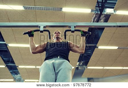 sport, fitness, lifestyle and people concept - young man doing pull-ups in gym