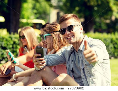 friendship, leisure, technology and people concept - smiling man with smartphones showing thumbs up in front of his friends