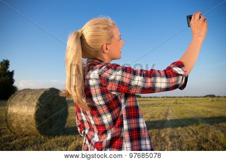 Beautiful Country Woman Making Selfie Photo On Smartphone In Field With Haystacks