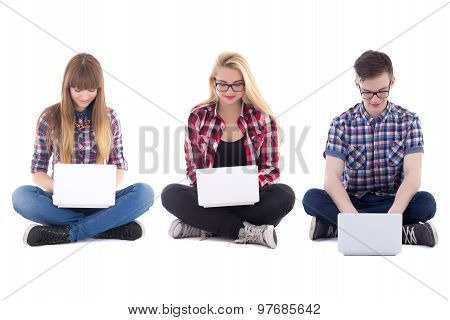 Two Teenage Girls And One Boy Sitting With Laptops Isolated On White