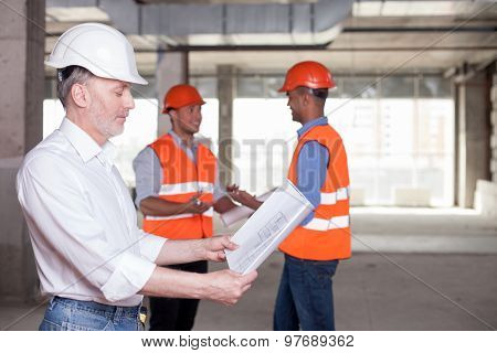 Cheerful construction team is discussing a new project