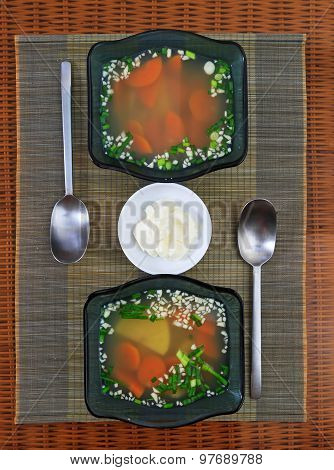 Two Glass Bowls With Vegetable Soup And A Saucer With Sour Cream