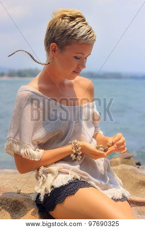 Young Woman Sitting On Picturesque Rocky Seashore