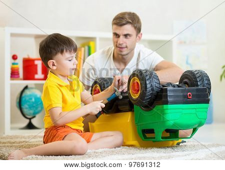 Child boy plays at home with truck toy closely watched by his father who is leaning over him