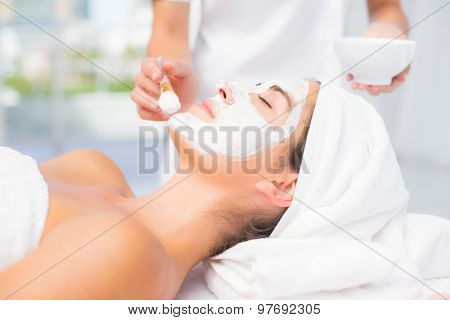Side view of an attractive woman receiving treatment at spa center
