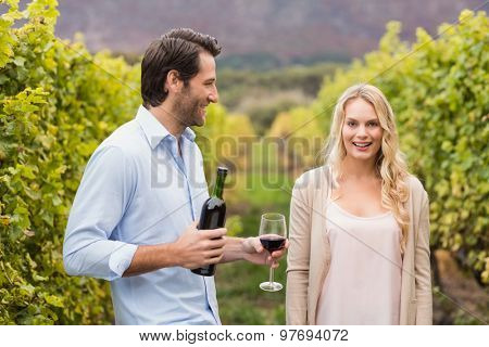 Young happy man offering wine to a young woman in the grape fields