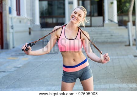 A pretty woman with a jumping rope on a sunny day