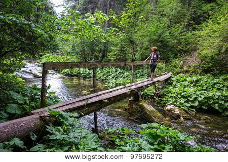 Woman Crossing The River On A Wooden Bridge