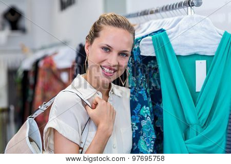 Portrait of smiling woman standing next to clothes rail in clothing store