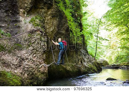 Backpacker On Safety Cables Over Water