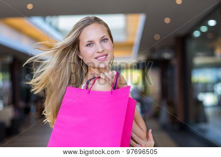 Portrait of smiling woman holding shopping bags at shopping mall
