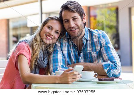 Smiling couple having tea in a cafe on a sunny day
