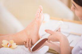 pic of wet feet  - Peeling feet pedicure procedure in a beauty salon. ** Note: Shallow depth of field - JPG