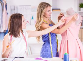 pic of dress mannequin  - Beautiful young women with measuring tape on shoulders working at pink dress on mannequin in studio - JPG