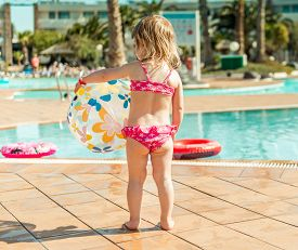 stock photo of pool ball  - little cute girl playing near the pool with a ball - JPG