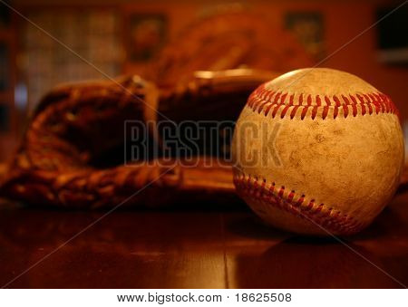 Close up of a baseball with a glove behind it.