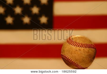 Close up of an old nostalgic baseball, with American flag background.