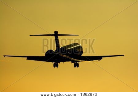 Silhouette Of Jet About To Touch Down Into The Setting Sun.