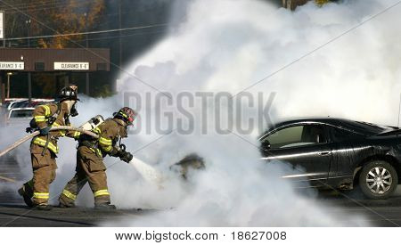 Firemen extinguishing a car fire.