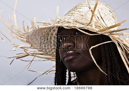 Young African woman with sun hat, dreadlocks hairstyle