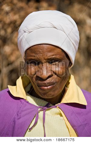 Old african woman in the village dressed in church uniform