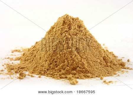 a one pile of ground ginger on white, bright yellow color, sharp shot.
