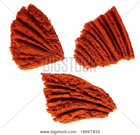 three piles of ground paprika on white, bright red color, sharp shot.