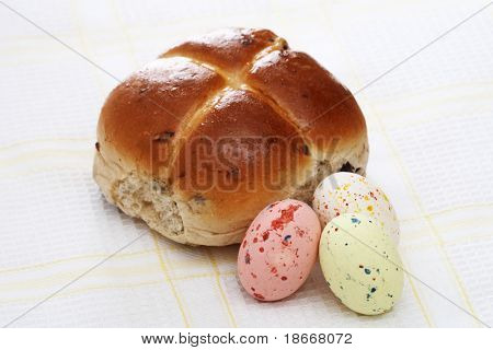 hot cross bun and three Speckled easter eggs on a tea-cloth