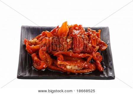 sun-dried tomatoes with olive oil on a plate, over white isolated