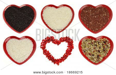 different sort of rice and goji berryes heart shape, bright red color, over white