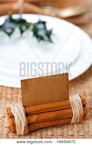 aromatic christmas place setting place  with card, holly twig in white plate, shallow dof
