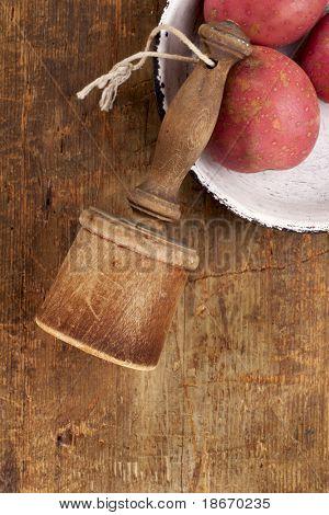retro potato masher on old wooden table with potato