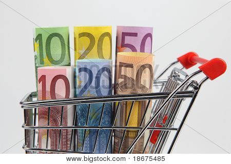 Mini shopping cart with euro banknotes on white background