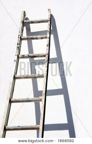 A Builders Ladder Propped Against A White Wall.