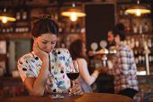 Upset woman ignoring affectionate couple in pub poster
