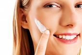Portrait of young woman applying moisturizer cream on her pretty face poster