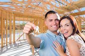 Young Military Couple On Site With House Keys Inside Their New Home Construction Framing. poster