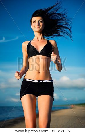 Attractive Woman Jogging On The Beach