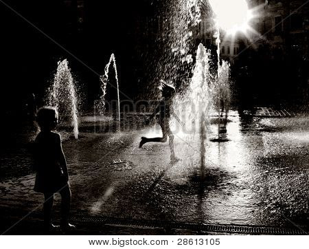 low sunlight hitting water fountain with silhouettes of playing children